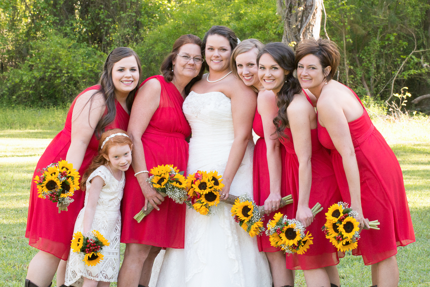 Red bridesmaids dresses and sunflowers at Adam's Pond