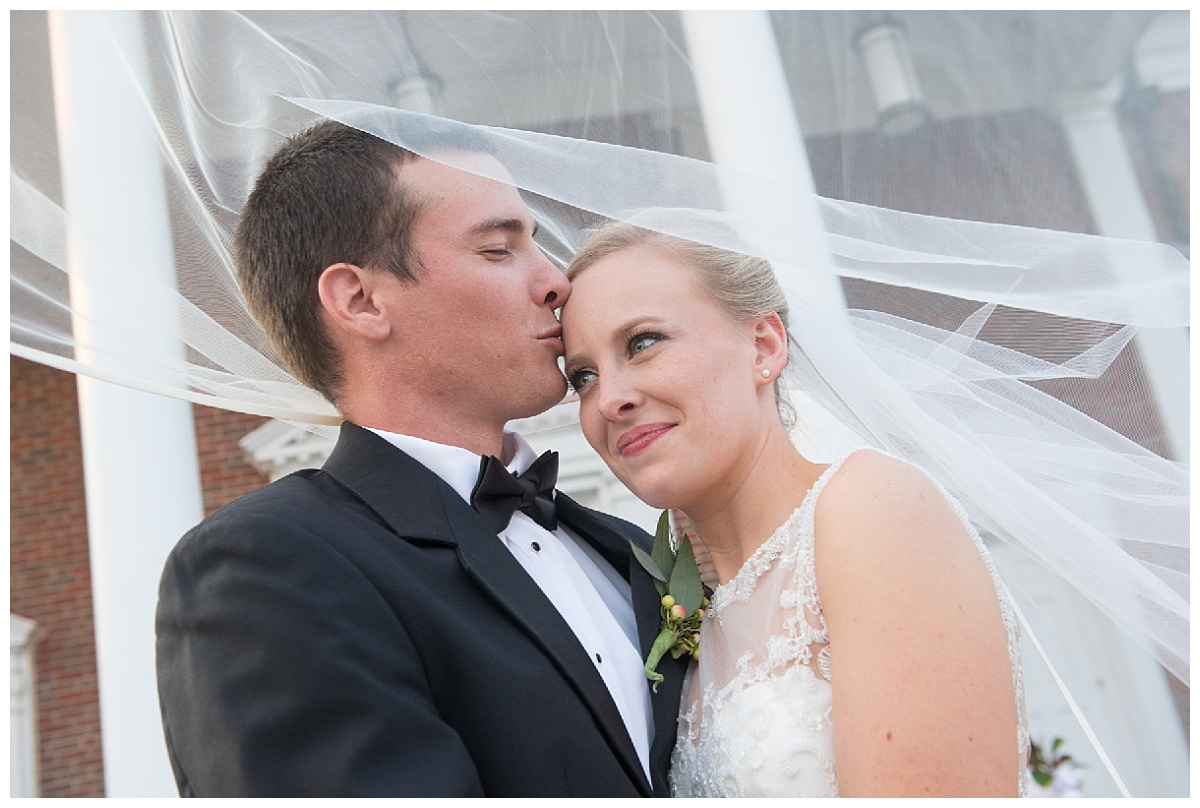 Groom kissing bride's forehead in a sweet portrait
